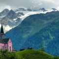 Roze kerk in Trient, Zwitserland: in een schilderachtige 'The Sound of Music'-setting in de Alpen ligt een dorpje met 161 inwoners. Wat dit dorp zo bijzonder maakt? De roze kerk met achterliggende bergen! © edwademd via Flickr Creative Commons