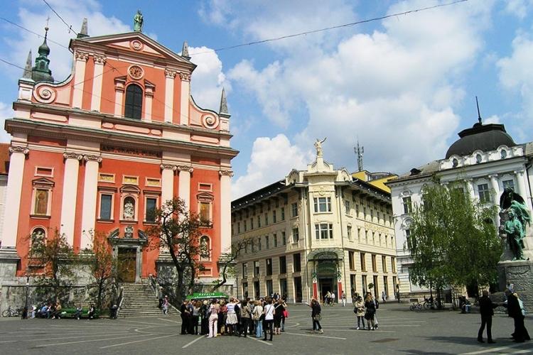 Fransiscaanse kerk van de Annunciatie in Ljubljana, Slovenië: als symbool voor de Franciscaanse kloosterorde werd dit heilig gebouw rood geschilderd. Midden op het centrale plein in Ljubljana heeft deze kerk dan ook zeker bekijk! © Wikimedia Commons