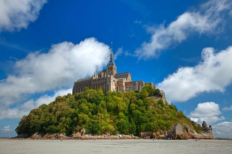 Kerk van Mont-Saint-Michel in Normandië, Frankrijk: de bekendste in het rijtje is waarschijnlijk de kerk op Mont-Saint-Michel. Bovenop het eiland kijkt dit gebouw uit op de getijden die deze plaats zo speciaal maken! © Nicolas Raymond via Flickr Creative Commons