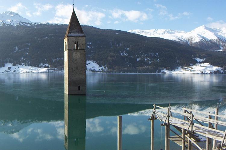 Verdronken kerk in Zuid-Tirol, Italië: de 14de-eeuwse toren van de kerk is het enige wat nog zichtbaar is van het kleine stadje dat in 1950 artificieel werd overspoeld. Wanneer het meer bevriest kan je de toren zelfs te voet bereiken! © Wikimedia Commons