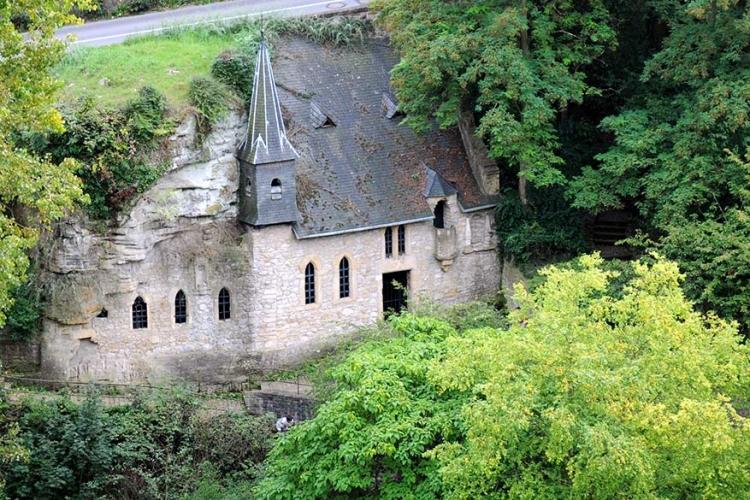 St. Quirin Kapel in Luxemburg: een kerk die nog meer geïntegreerd staat in de rotsen is de St. Quirin kapel in Luxemburg. Lijkend op een huis voor hobbits bestaat dit gebouw grotendeels uit heuvel en rots! © Wikimedia Commons