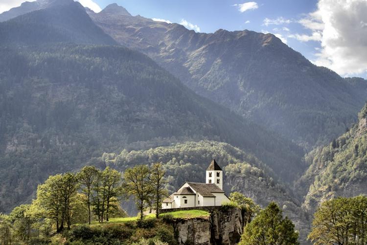 San Martino Kerk in Calonico, Zwitserland: een echte cliffhanger is deze kerk, letterlijk dan. De San Martino kerk vind je op de rand van een 30 meter hoge klif, uitkijkend op de uitgestrekte Leventina vallei. © Wikimedia Commons