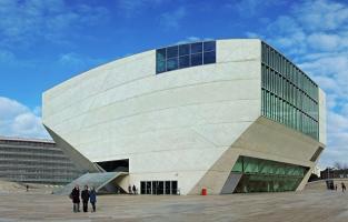 2. Bewonder moderne architectuur: hoe charmant en authentiek de huisjes en gebouwen eruitzien in het centrum van Porto aan de Douro, des te moderner zijn de bouwwerken aan de rand van de stad. Een voorbeeld is Casa da Música, een groot concertgebouw ontworpen door de Nederlandse architect Rem Koolhaas. In 2001, toen Porto Culturele Hoofdstad van Europa was, moest het gebouw eigenlijk klaar zijn, maar de officiële opening liet op zich wachten tot in 2005. © Wikimedia Commons