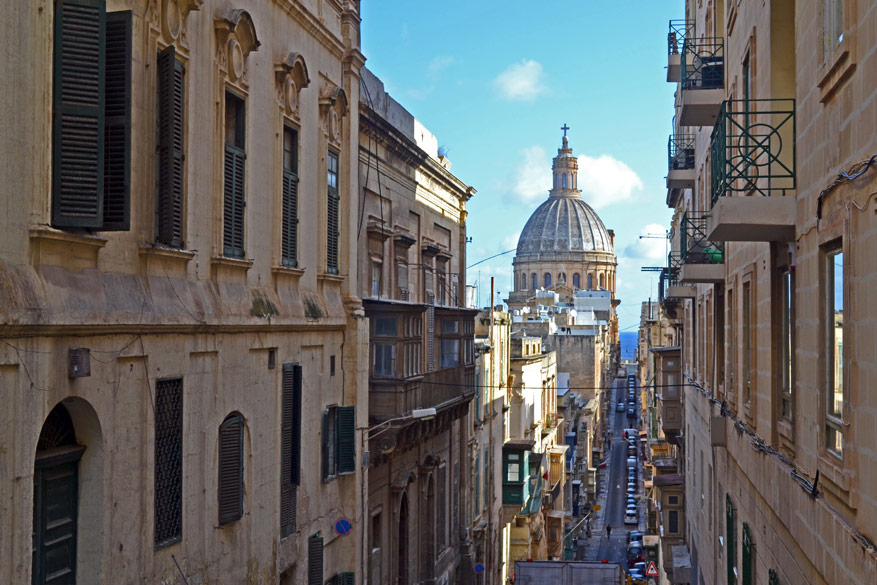 In de binnenstraatjes vangen we een glimp op van de iconische Basilica of Our Lady of Mount Carmel die Valletta's skyline tekent.